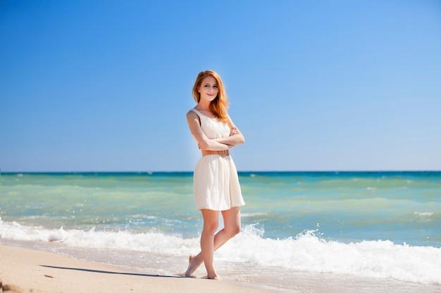 Молодая рыжая девушка на пляже.