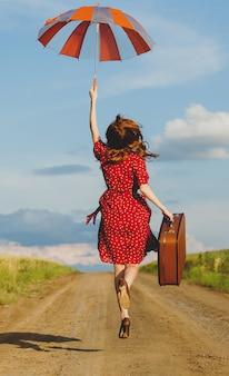 フィールドの近くの道路上のスーツケースを持つ美しい若い女性の写真