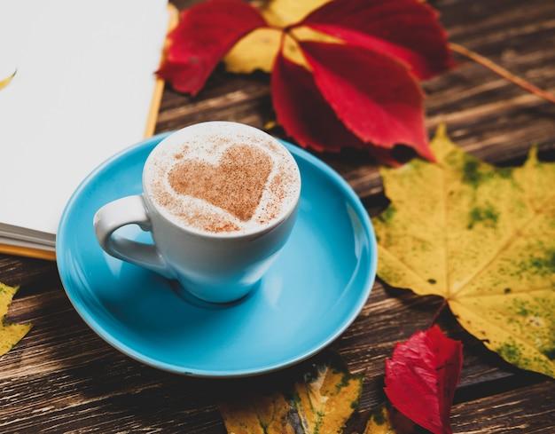Листья осени, книга и кофейная чашка на деревянном столе.
