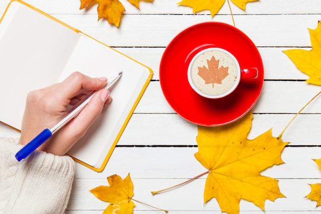 女性開き手左右一杯のコーヒーの近くのノートに何かを書く。