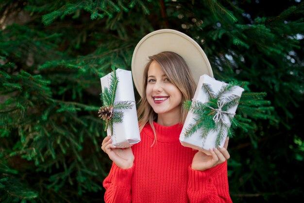 Женщина в красном свитере с рождественскими подарками возле сосны