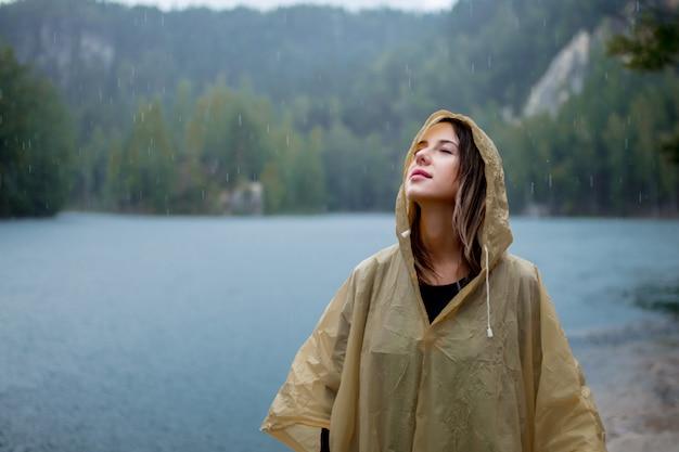 雨の日の湖の近くのレインコートの女性。