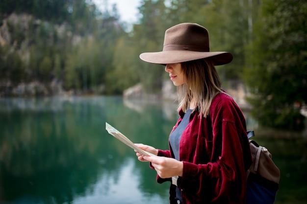 湖の近くの地図と帽子と赤シャツの若い女性