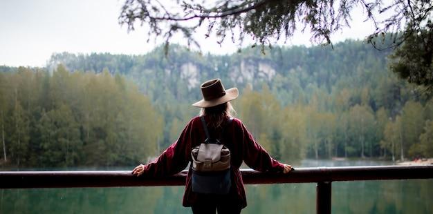山の湖の近くの帽子と赤シャツの女性。