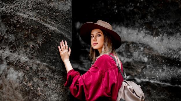 山の石の近くの帽子と赤シャツの女性