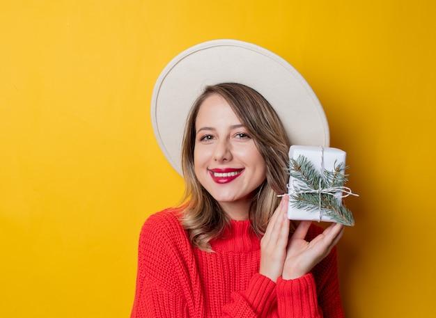 Молодая удивленная женщина в красном свитере с подарочной коробкой