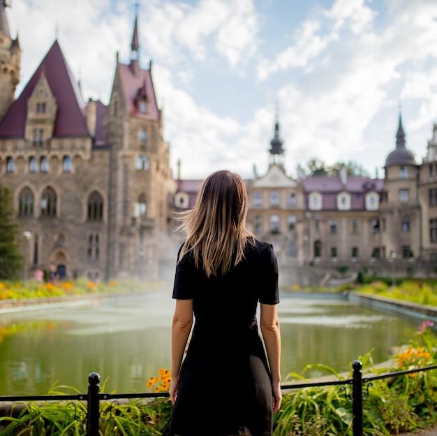 女性は城のある庭に滞在