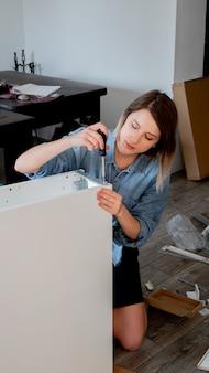 Женщина с отверткой лично устанавливает мебель у себя дома