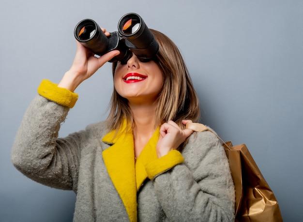 ショッピングバッグと双眼鏡のコートの女性