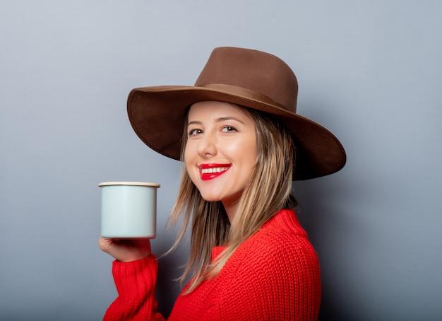 赤いセーターと一杯のコーヒーと帽子の女性