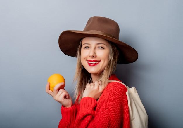 オレンジとバッグの赤いセーターの女性