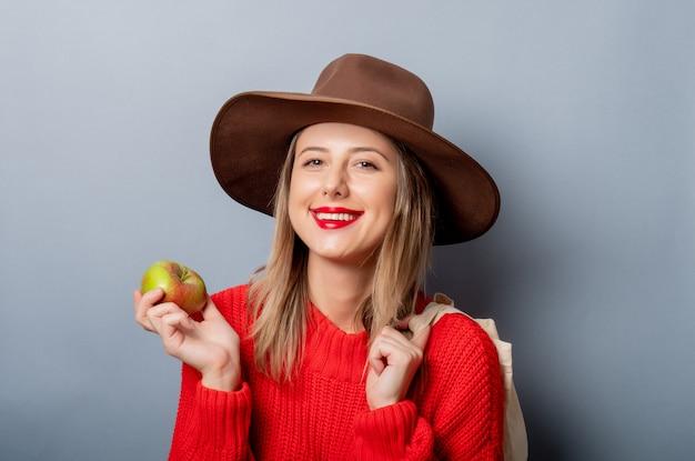 アップルとバッグの赤いセーターの女性