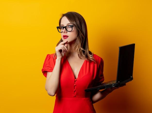 黄色の壁にラップトップコンピューターと赤いドレスで美しい女性