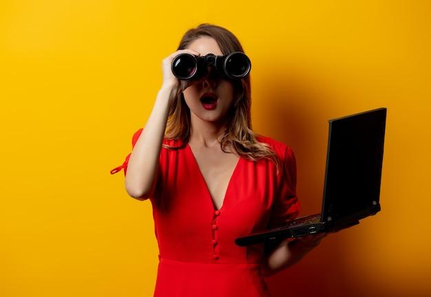 双眼鏡とラップトップコンピューターと赤いドレスの女