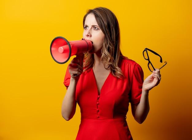 スピーカーと赤いドレスで美しい女性