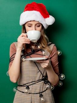 クリスマスライトと緑の壁にコーヒーのカップを持つ女性