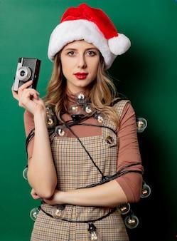 クリスマスライトと緑の壁にビンテージカメラを持つ女性
