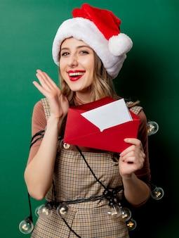 クリスマスの帽子と封筒のメールの女性