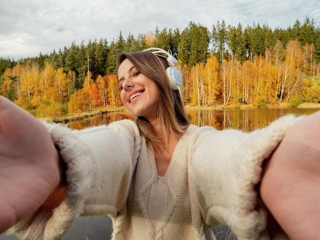 秋の時間で湖の近くのヘッドフォンを持つ女性