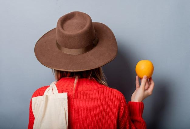 Женщина в красном свитере с апельсином и сумкой