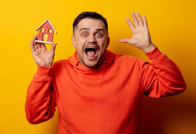Забавный человек с игрушечным домиком на желтой стене