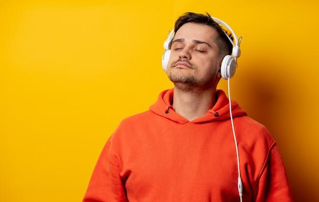 Забавный человек с наушниками на желтой стене