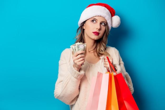 ショッピングバッグと青い壁にお金時計と美しい女性
