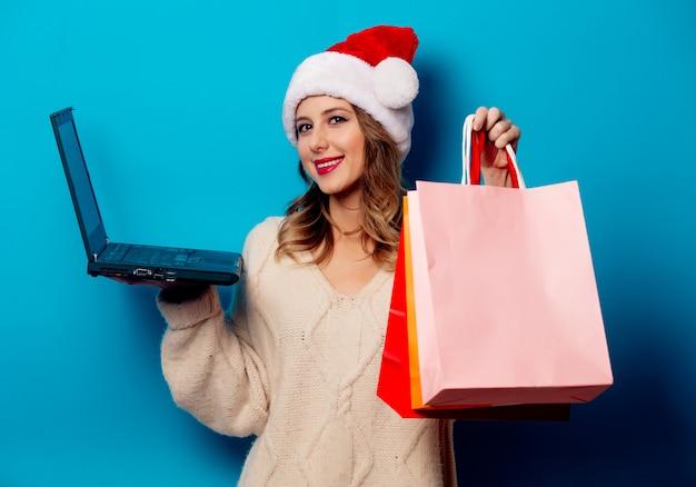 ショッピングバッグと青い壁にラップトップコンピューターを持つ美しい女性