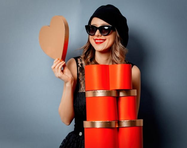 Молодая женщина с подарочными коробками на серой стене