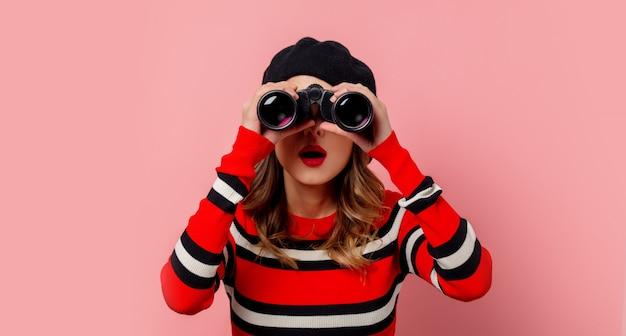 Молодая женщина в свитере с биноклем на розовой стене