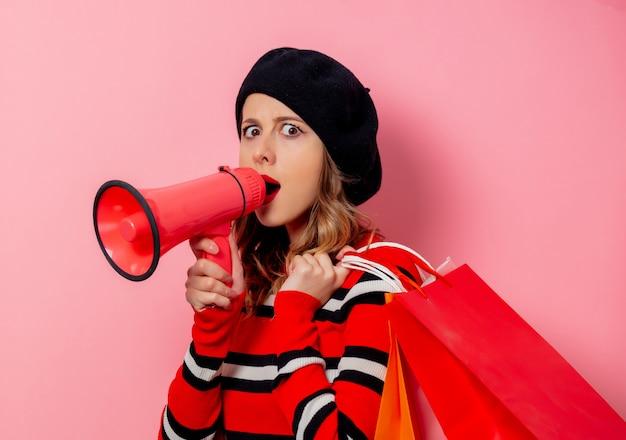 Молодая женщина с хозяйственными сумками и громкоговорителем на розовой стене