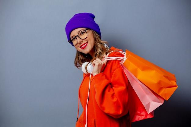 オレンジ色のパーカーと灰色の壁に買い物袋と紫の帽子のスタイルの女の子