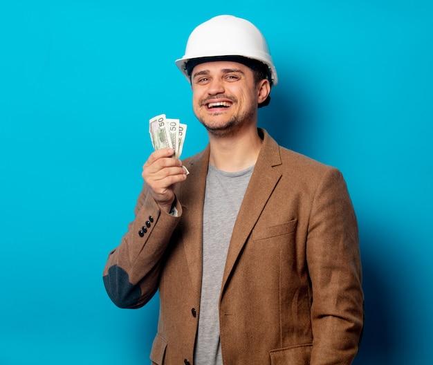 給与とヘルメットの若い男