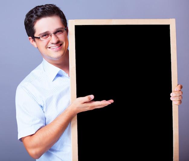 黒板を持つハンサムな男。