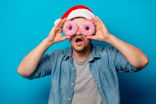 Красивый мужчина в рождественской шапке с пончиками