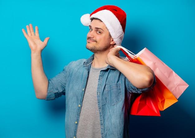 買い物袋とクリスマス帽子でハンサムな男