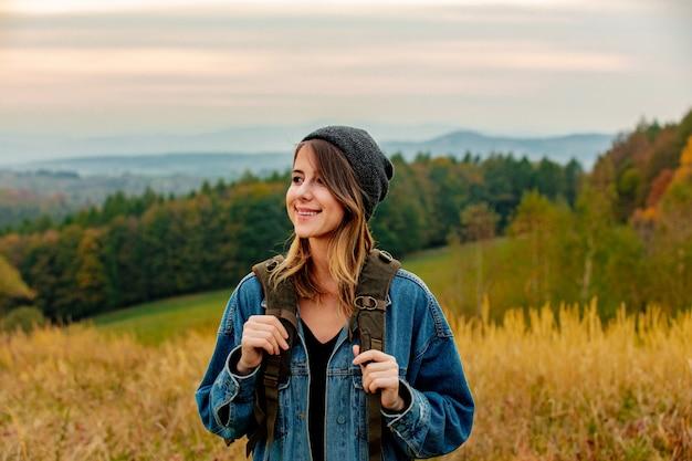 デニムジャケットと山と田舎のバックパックと帽子のスタイルの女性