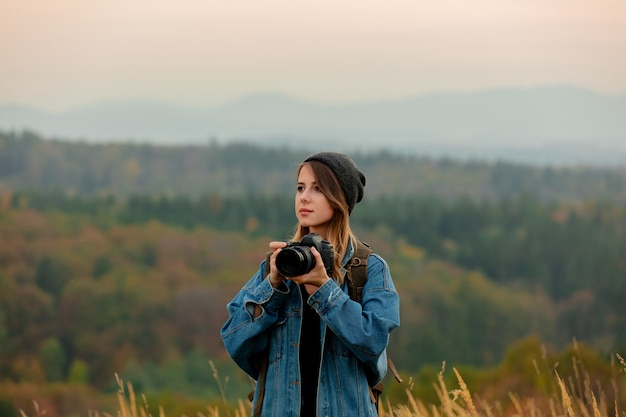 Стиль женщина с фотоаппаратом и рюкзаком в сельской местности с горами