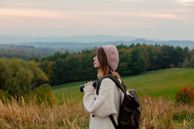 双眼鏡と田舎でバックパックのスタイルの女性