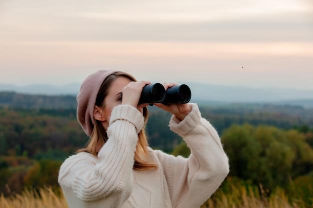 山の田舎で双眼鏡を持つスタイルの女性
