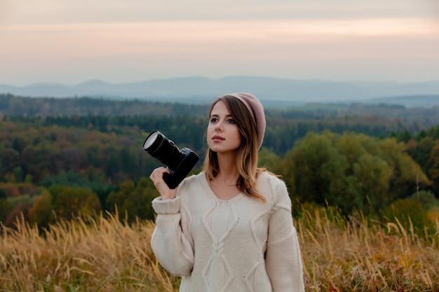 山の田舎で写真カメラを持つスタイルの女性