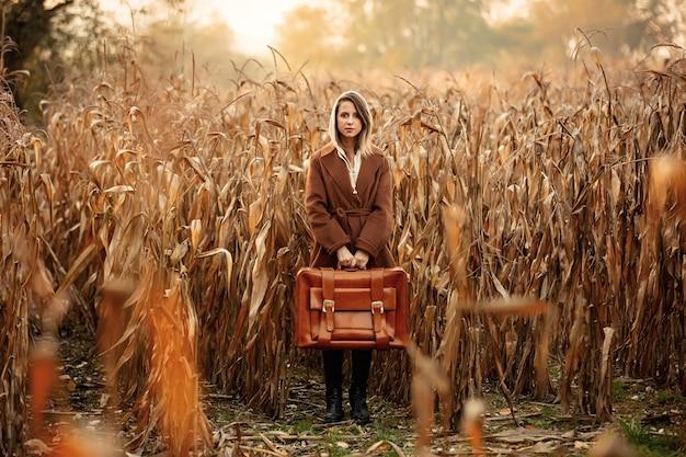 秋の時間の季節にトウモロコシ畑にスーツケースとコートのスタイルの女性