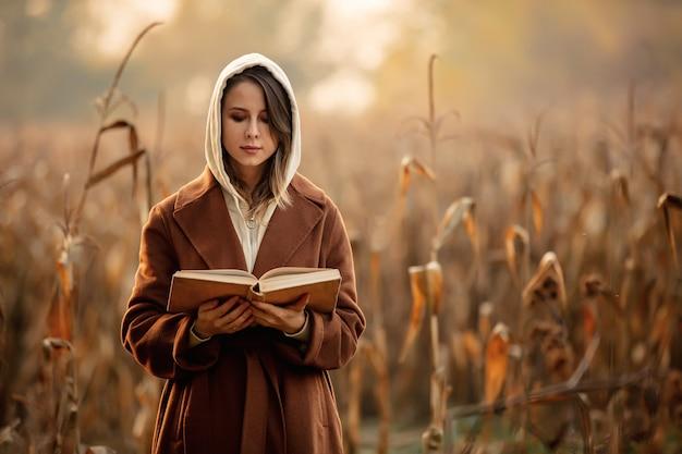 秋の季節にトウモロコシ畑の本とスタイルの女性