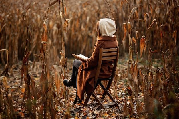 秋の時間の季節にトウモロコシ畑の椅子に座って本のスタイルの女性
