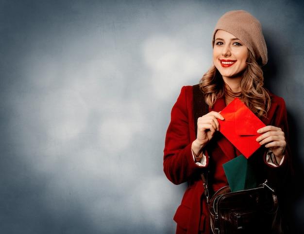 赤い封筒を持つ若い女性郵便屋さん