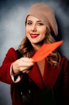 Почтальон молодой женщины с красным конвертом