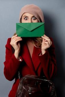 緑の封筒を持つ若い女性郵便屋さん