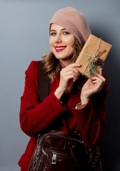 Женщина почтальон с подарочной коробкой