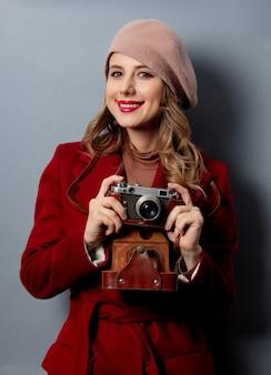 写真のカメラと赤いコートの若い女性