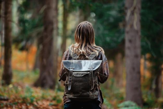 秋の森のバックパックを持つ女性